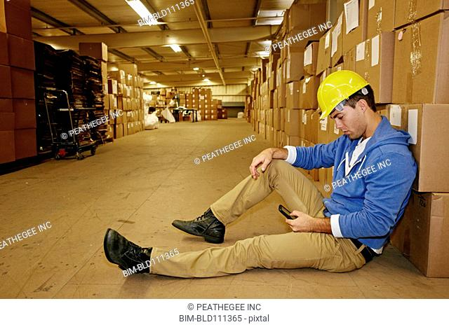 Caucasian worker using cell phone in warehouse