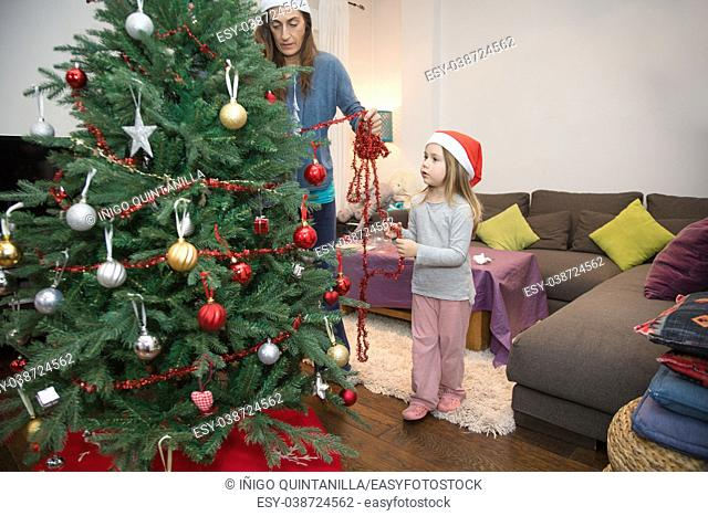woman decorating a Christmas tree at home with four years blonde cute child with red Santa Claus hat