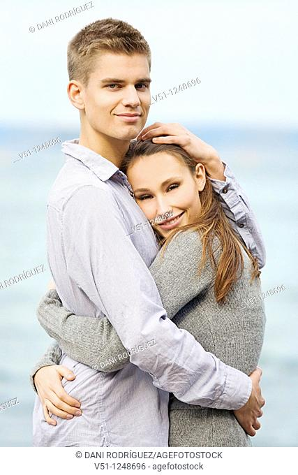Portrait of a young couple holding by the sea