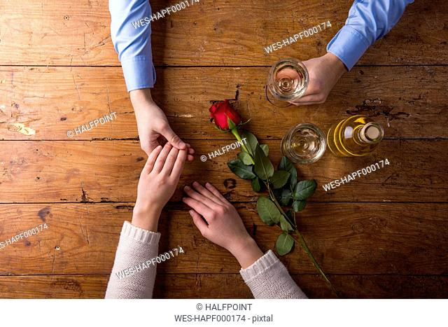 Hands of a young couple with red rose and a bottle of white wine