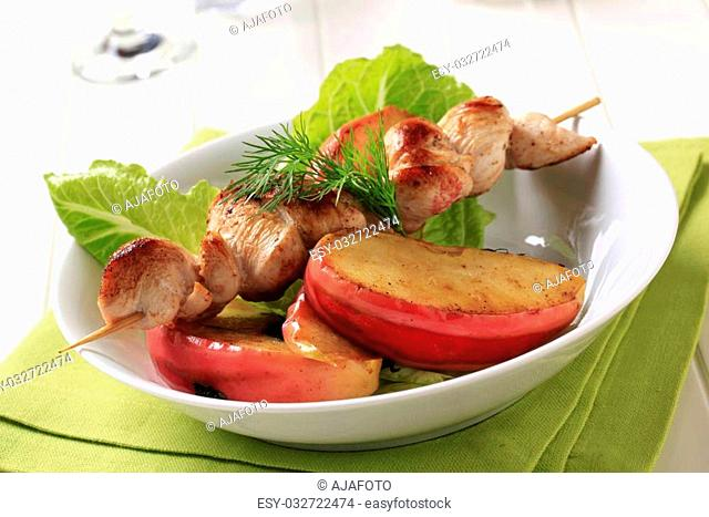 Chicken skewer with slices of baked apple