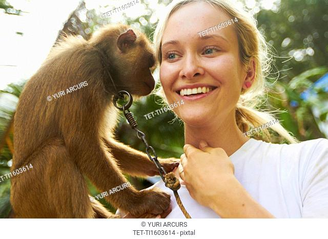 Portrait of young woman holding macaque monkey