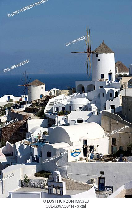 View of white washed hillside town and windmill, Oia, Santorini, Cyclades, Greece