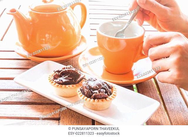 Hot cup of white tea and crispy chocolate tarts