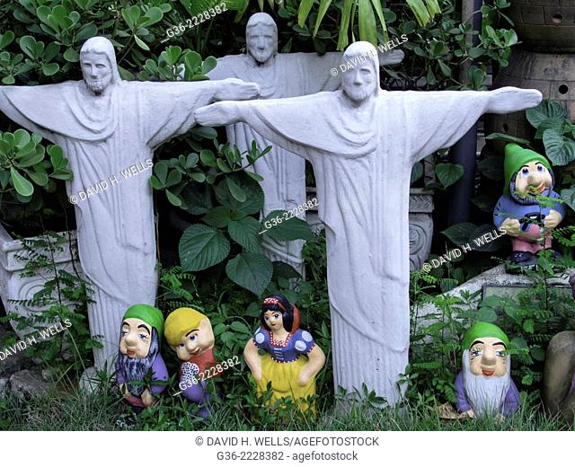 Garden gnome and Christ the redeemer statue on grass, Gávea, Rio De Janerio, Brazil