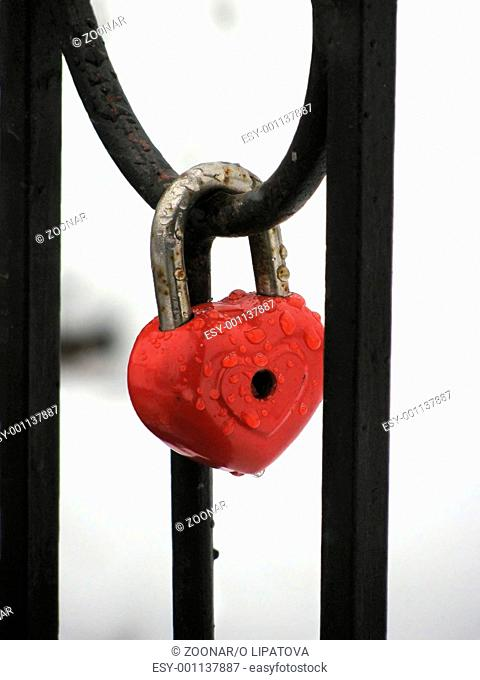 Red heart lock with the drops of rain. Metal fence