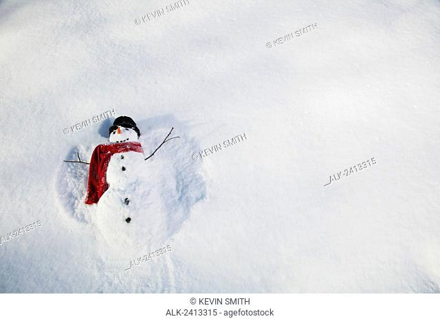 Snowman wearing a red scarf and black top hat making snow angels in the snow, Russian Jack Springs city park, Anchorage, South Central Alaska, Alaska, USA