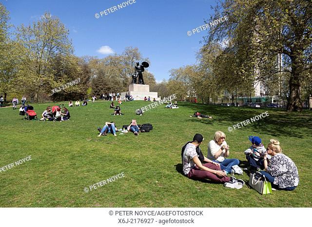 People enjoying the sunshine around Achilles Statue at Hyde Park Corner. London