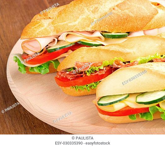 three sandwiches with savoury fillings on a cutting board