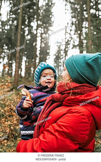 Mother carrying little daughter in autumnal forest