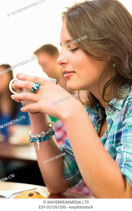 Close up of female having coffee and muffin at coffee shop