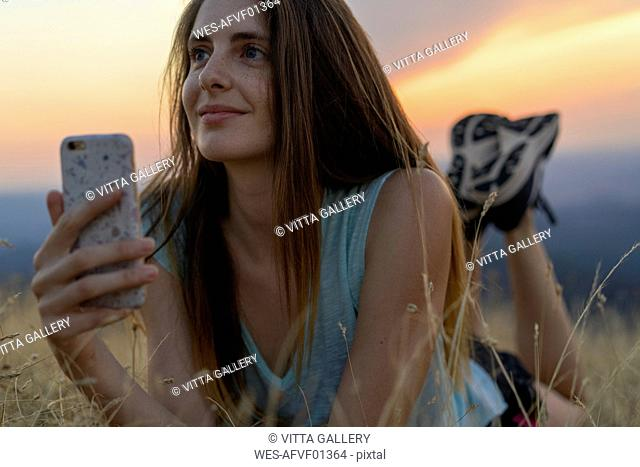 Smiling young woman with cell phone lying in grass during sunset