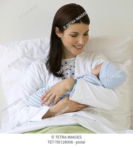 Mother holding newborn in hospital