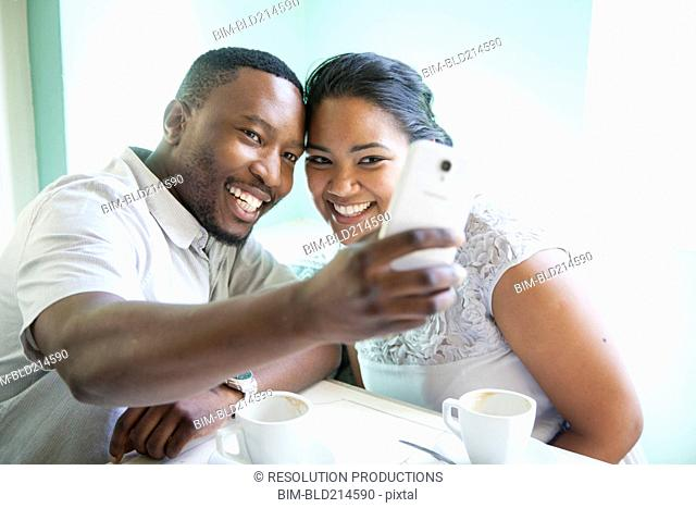 Smiling couple taking cell phone selfie