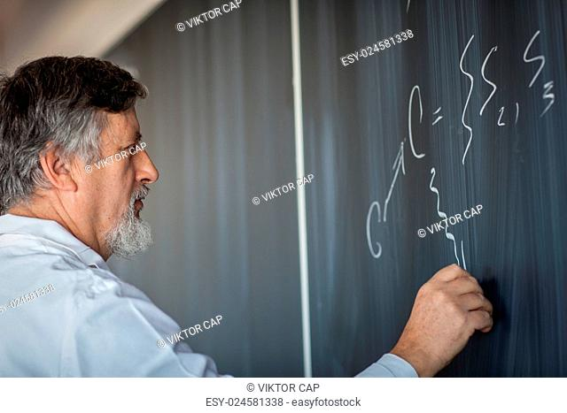 Senior chemistry professor writing on the board while having a chalk and blackboard lecture (shallow DOF color toned image)