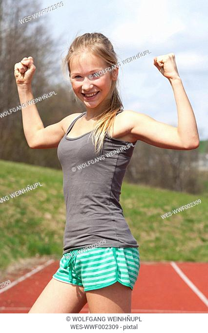 Austria, Teenage girl on track showing her muscles, smiling, portrait