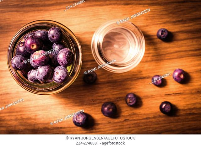 Blueberry food photo on a jar of fresh and ripe berries on wooden kitchen bench