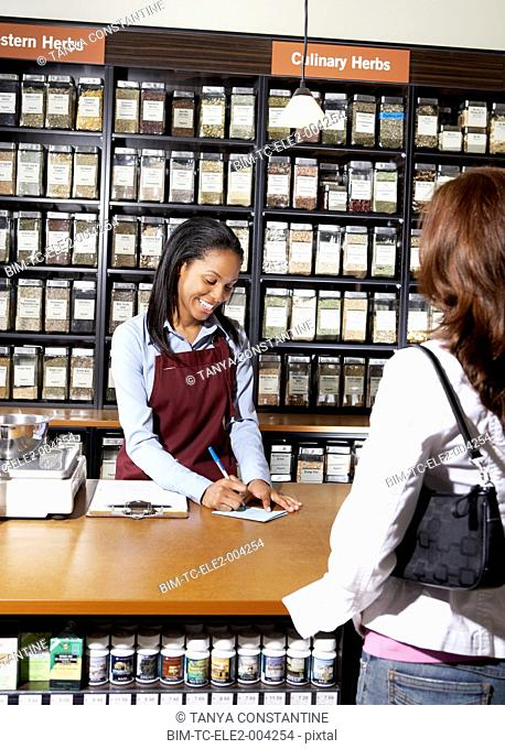 African saleswoman filling out sales slip for customer at herb store