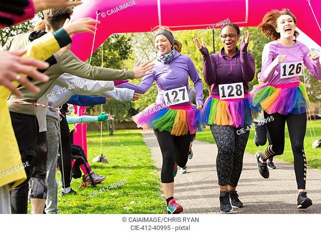 Spectators high-fiving female runners in tutus crossing charity run finish line