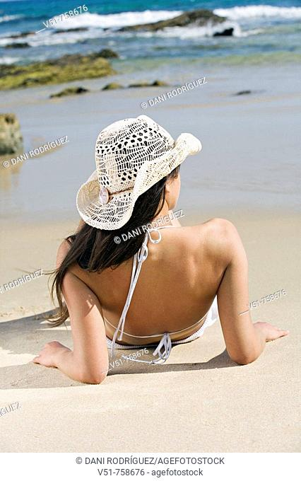Young woman sunbathing in the beach