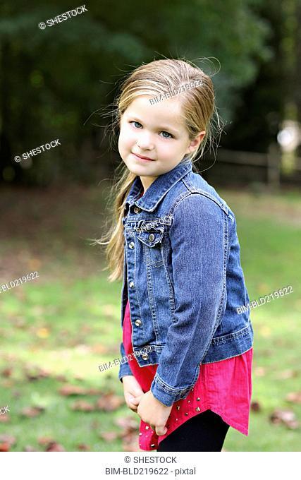 Serious girl standing in rural field
