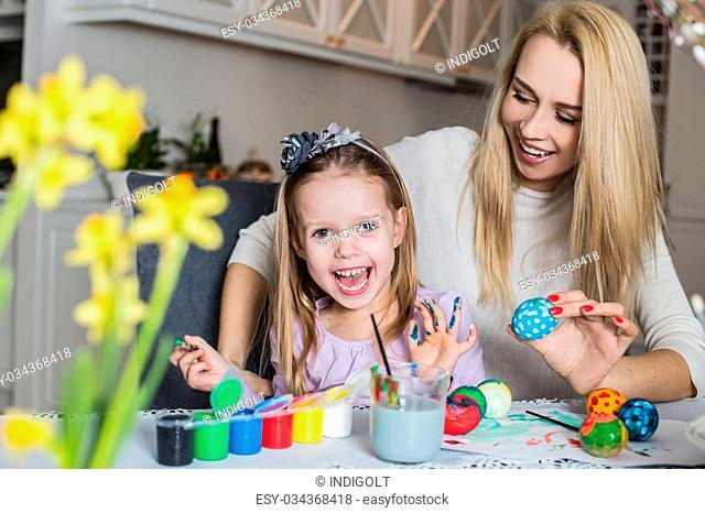 Happy mother and daughter painting easter eggs in the living room. Easter, family, holiday and child concept