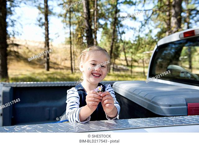 Caucasian girl playing in truck bed