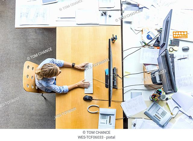 Top view of woman using computer at desk in office surrounded by documents