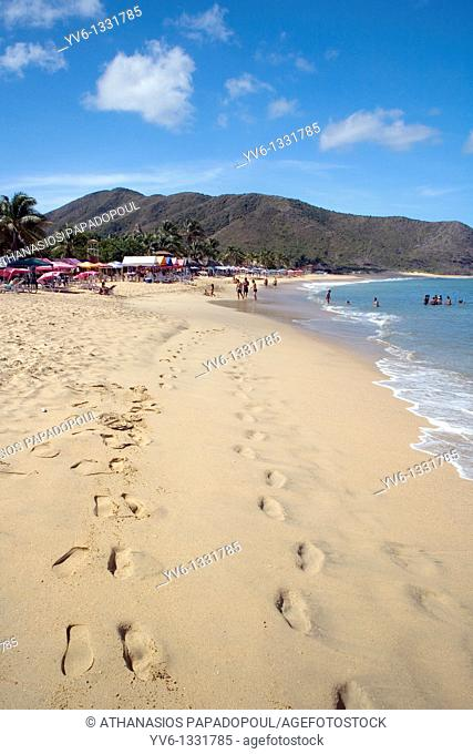 "View of ""Playa Caribe"" exotic beach with footstep marks on the sand leading to people swimming and walking on the sand while deck chairs"