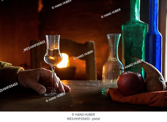 Hand with shot glass and bottles in front of open fire