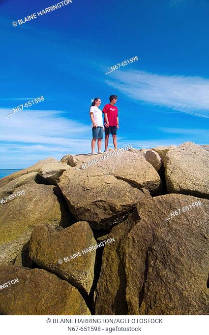 12 year old girl and her 15 year old brother standing on the rocks at Rock Harbor, Orleans, Cape Cod, Massachusetts, USA