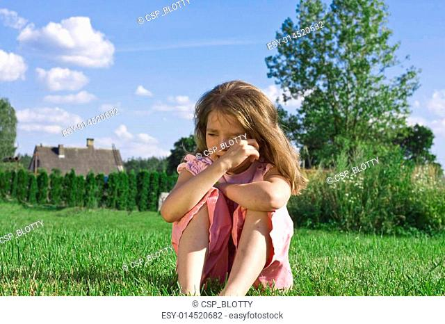Crying little girl sitting on grass