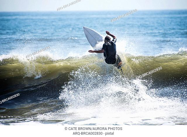 Rear view of surfer in wetsuit riding wave in sea