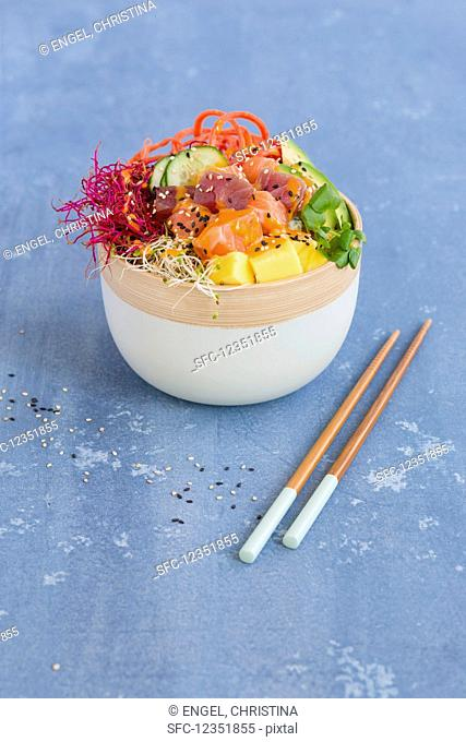 A Poke bowl with tuna, salmon, sushi rice, tobiko, avocado, carrots, mango, and sprouts