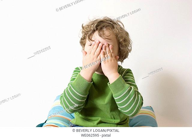 Three-year-old boy covering his eyes