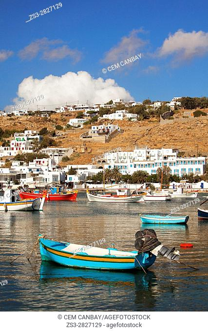 Colorful traditional fishing boats inside the harbor with the whitewashed traditional houses at the background, Mykonos, Cyclades Islands, Greek Islands, Greece
