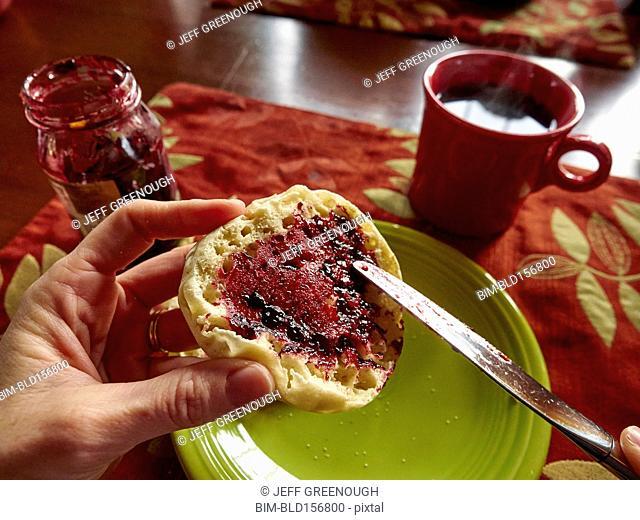 Caucasian boy spreading jam on english muffin