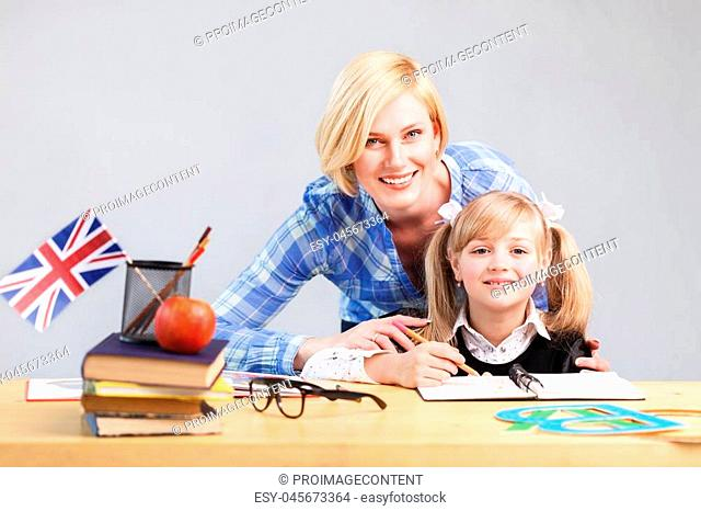 Teacher helps kid girl to learn English language, school table with books, flag and letters in light classroom