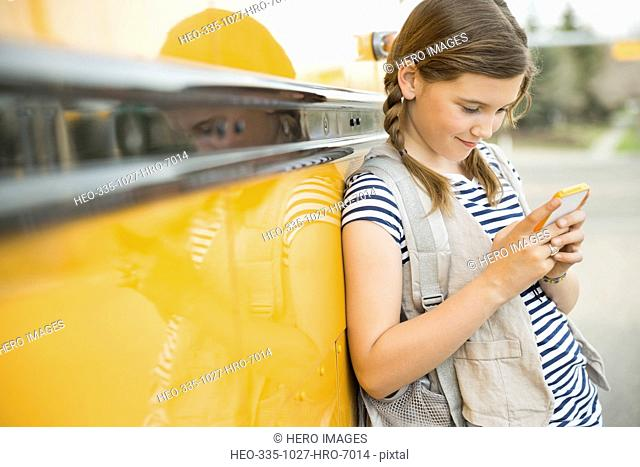 Little girl text messaging through mobile phone by school bus