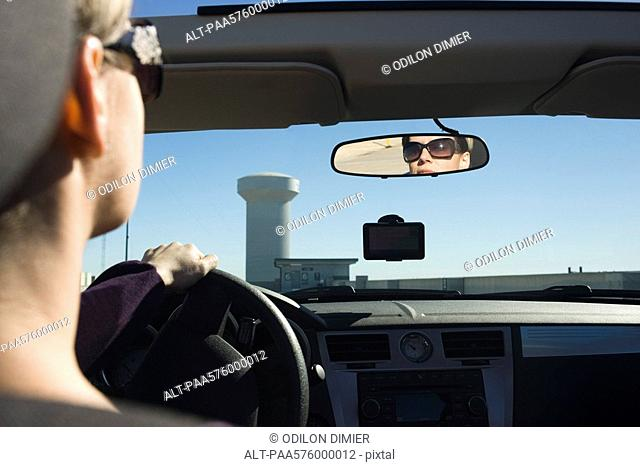 Woman driving, reflection in rearview mirror