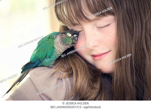 Portrait of girl (13-15) cuddling with parrot