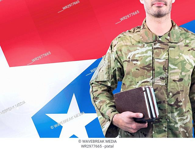 Soldier holding books in front of the american flag