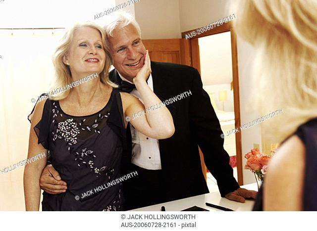 Reflection of a mature woman admiring a mature man in a mirror