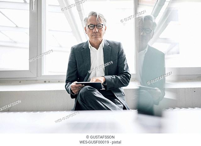 Portrait of confident senior businessman using tablet