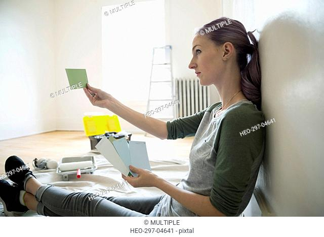 Woman holding paint swatches in living room