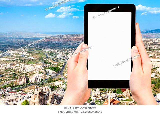 travel concept - tourist photographs of Uchisar village and roads in valley in Nevsehir Province in Cappadocia in spring in Turkey on smartphone with cutout...