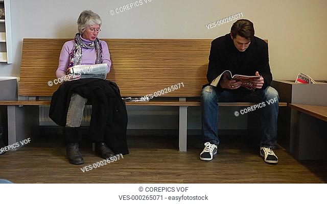 An elderly woman caressing her bandaged arm sitting on a wooden bench next to a young man reading a magazine in the waiting room of a general medical practice