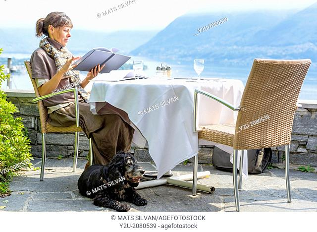 Woman in a restaurant and reading the menu in ascona ticino switzerland