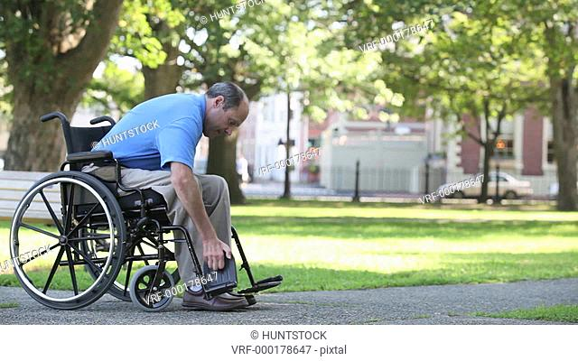 Man in a wheelchair with Friedreich's Ataxia trying to adjust foot pedals with atrophied hands and greeting friend