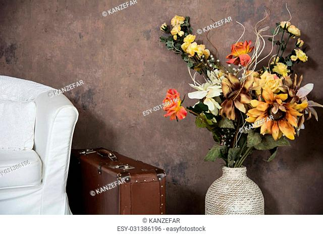 Design vintage interior with flowers in a vase suitcases and chairs. Old room